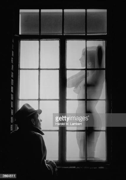 A man wearing a hat and coat stands outside a window at night and watches a woman undress circa 1960s