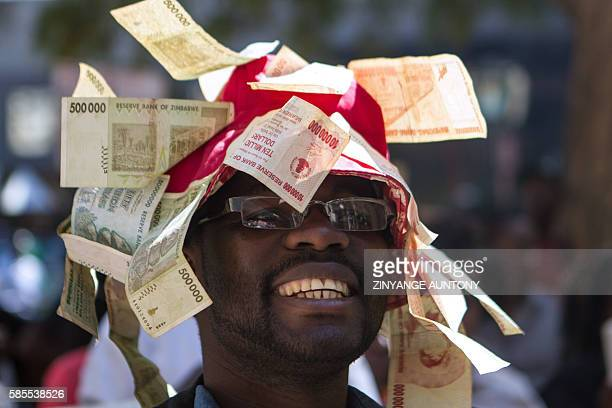 A man wearing a hat decorated with worthless note bearers' cheques during a protest against government plans to introduce bond notes a local token...