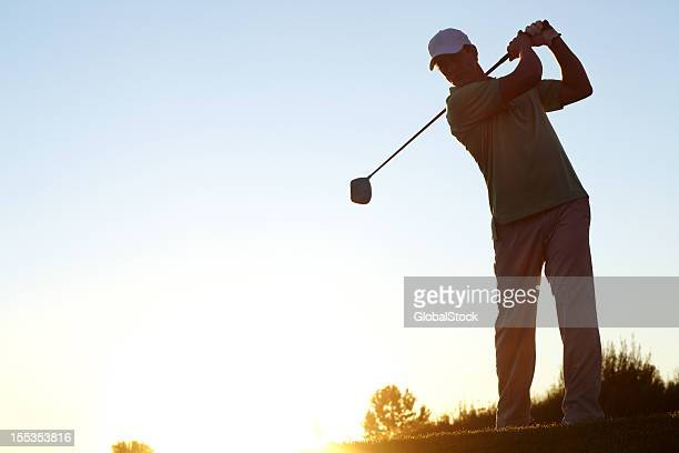 Man wearing a hat playing golf at sunset