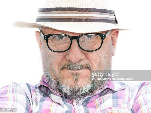 Man wearing a hat watching at camera