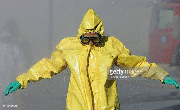 A man wearing a hazardous materials suit walks through a decontamination shower during a weapons of mass destruction training workshop February 1...
