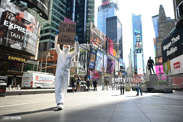 A man wearing a hazmat suit and a mask holds a sign reading the end is near call grandma at Times Square on March 14 2020 in New York City The World...