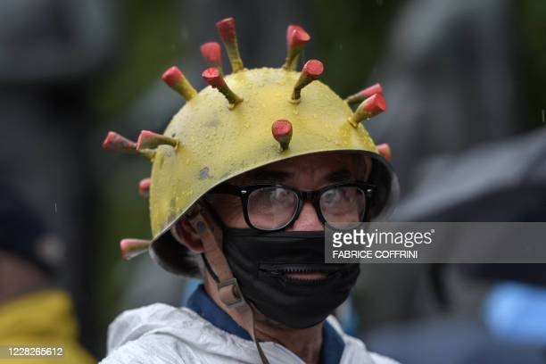 Man wearing a helmet, made to look like the common image of a corona virus, takes part to a protest against the increasing requirements in Swiss...