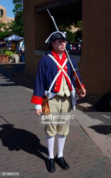 A man wearing a homemade Revolutional War soldier uniform poses for photographs at a Fourth of July celebration in Santa Fe New Mexico