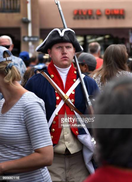 A man wearing a homemade Revolutionary War uniform and carrying a wooden rifle mingles with the crowd and poses for photographs at a Fourth of July...