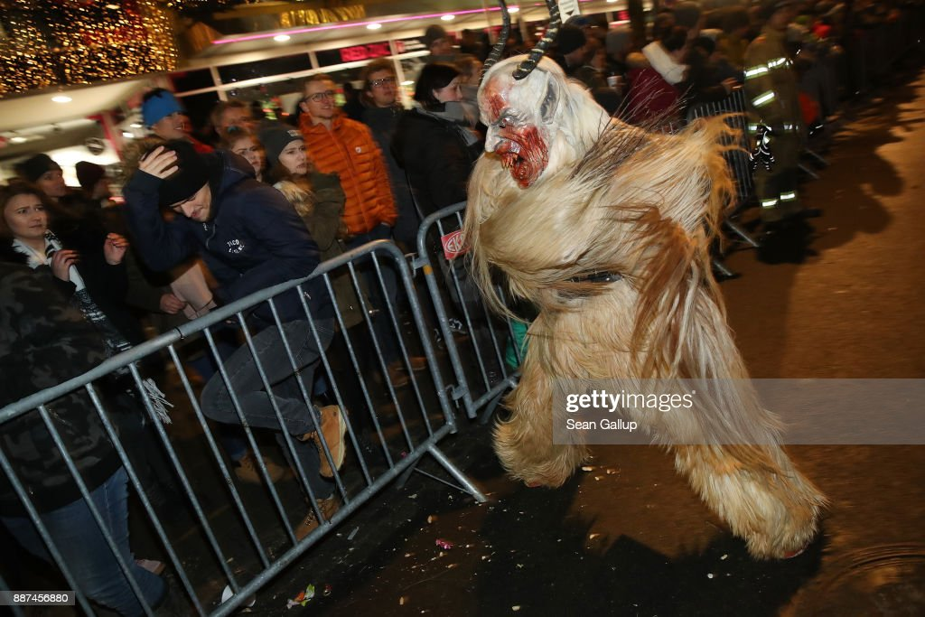 A man wearing a horned, wooden mask and dressed as the Krampus creature swats at bystanders with a switch made of branches during the annual Krampus parade on Saint Nicholas Day on December 6, 2017 in Sankt Johann im Pongau, Austria. Several hundred Krampus creatures from the region took part in this year's Sankt Johann parade. Krampus traditionally accompanies Saint Nicholas and angels in a house to house procession to reward children who have been good and warn those who have not, though in recent decades Krampus parades have become an intrinsic part of local folklore and take place throughout the end of November and into the first half of December in the alpine regions of Germany, Austria and Italy. Krampus usually wears large cowbells on his back that he rings by shaking his hips to ward off the evil spirits of winter. He also carries a switch made of branches or animal hair that he uses to whip bystanders.