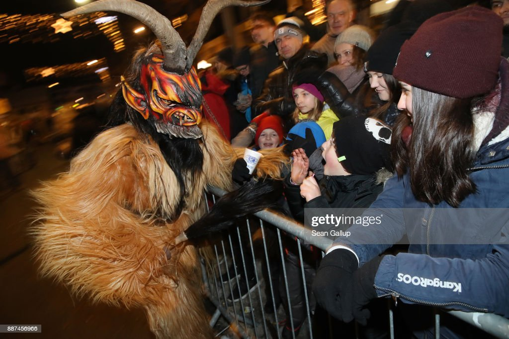 A man wearing a horned, wooden mask and dressed as the Krampus creature brandishes a switch made of animal hair towards bystanders during the annual Krampus parade on Saint Nicholas Day on December 6, 2017 in Sankt Johann im Pongau, Austria. Several hundred Krampus creatures from the region took part in this year's Sankt Johann parade. Krampus traditionally accompanies Saint Nicholas and angels in a house to house procession to reward children who have been good and warn those who have not, though in recent decades Krampus parades have become an intrinsic part of local folklore and take place throughout the end of November and into the first half of December in the alpine regions of Germany, Austria and Italy. Krampus usually wears large cowbells on his back that he rings by shaking his hips to ward off the evil spirits of winter. He also carries a switch made of branches or animal hair that he uses to whip bystanders.