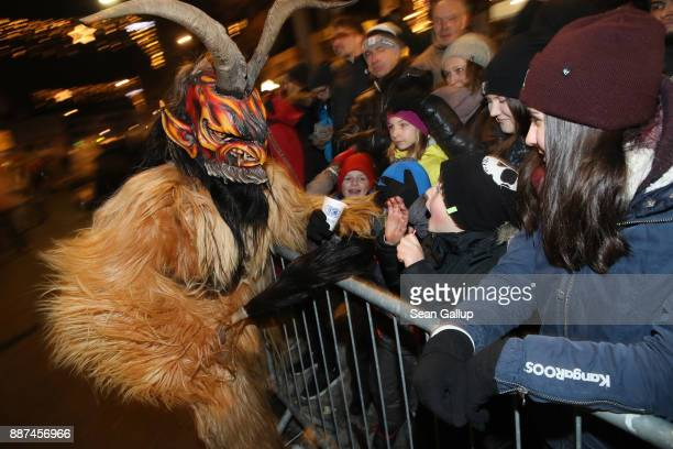 A man wearing a horned wooden mask and dressed as the Krampus creature brandishes a switch made of animal hair towards bystanders during the annual...