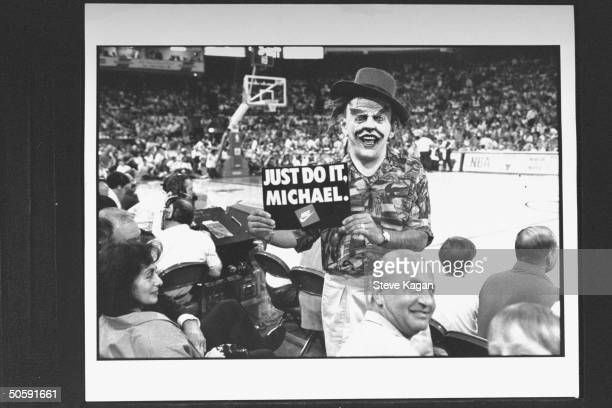 Man wearing a Jack Nicholson Joker mask of Batman movie fame as he holds up a JUST DO IT MICHAEL sign in the bleachers as he exhorts Chicago Bulls'...