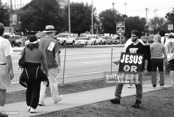 A man wearing a 'Jesus or Hell' sign hands out religious literature to race fans outside the speedway prior to the start of the 2003 Daytona 500...