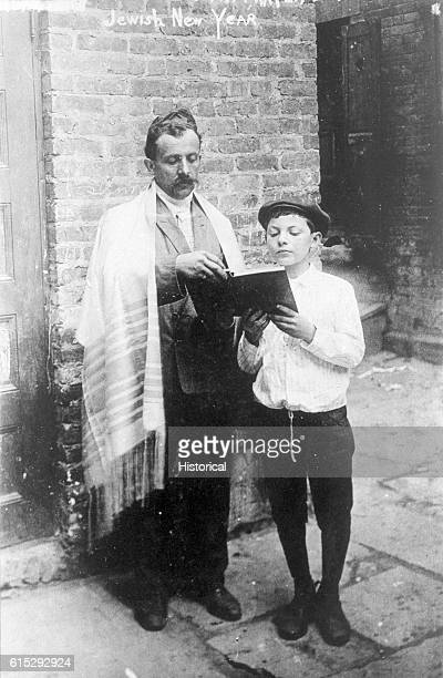 A man wearing a Jewish prayer shawl joins a boy in prayer at the Jewish New Year in New York City 1907