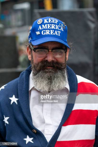 """Man wearing a """"Keep America Great"""" hat poses with his dog in Times Square on October 25, 2020 in New York City. The pandemic has caused long-term..."""