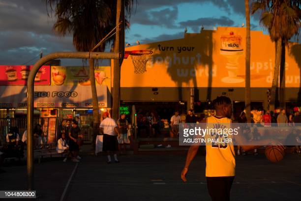 TOPSHOT A man wearing a LeBron James Los Angeles Lakers shirt plays basketball at Venice Beach California on September 30 2018 LeBron James dazzled...