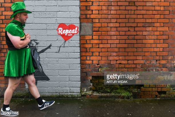 A man wearing a leprechaun dress walks in front of a prochoice mural based on a work by Banksy urging a yes vote in the referendum to repeal the...