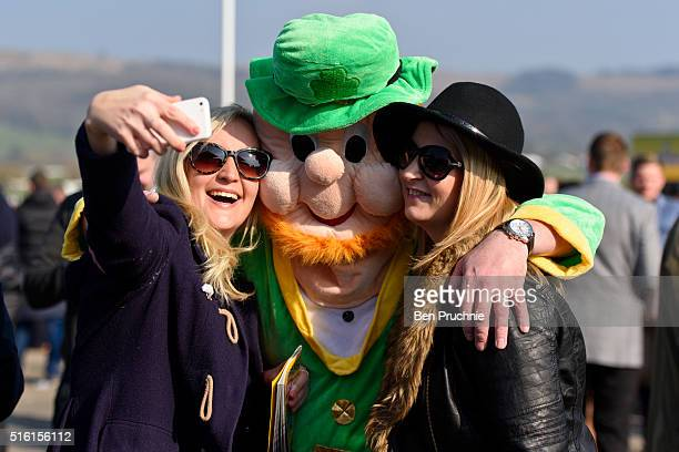 A man wearing a leprechaun fancy dress suit poses for a selfie during St Patrick's Day at the Cheltenham Festival at Cheltenham Racecourse on March...