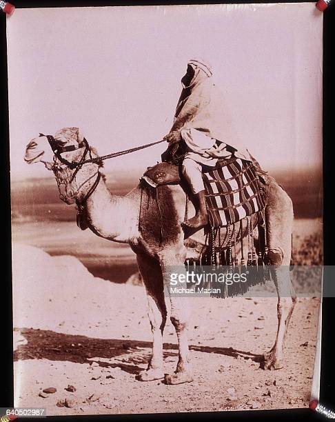 A man wearing a long protective headdress sits on a camel covered with a tasseled blanket Circa 18701890