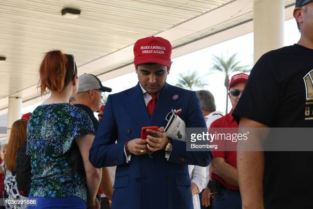 A man wearing a Make America Great Again hat looks at a smartphone as attendees wait to join a rally with US President Donald Trump at the Las Vegas...