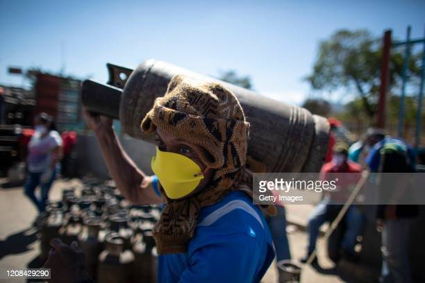 Man wearing a makeshift mask carries a butane gas cylinder on his back in a popular neighborhood south of the city during the second week of the...