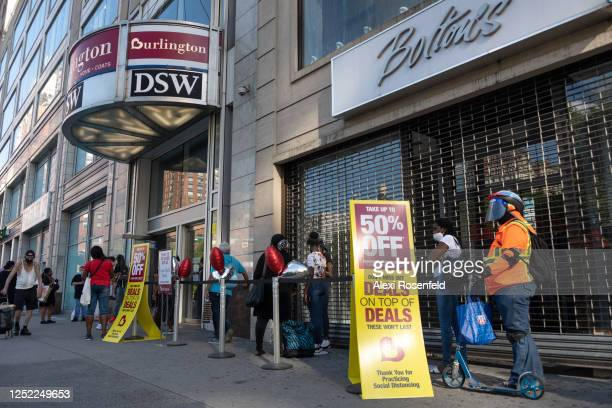 Man wearing a mask and face shield stands in line at near a 50% off sign at Burlington Coat Factory in Union Square as the city moves into Phase 2 of...