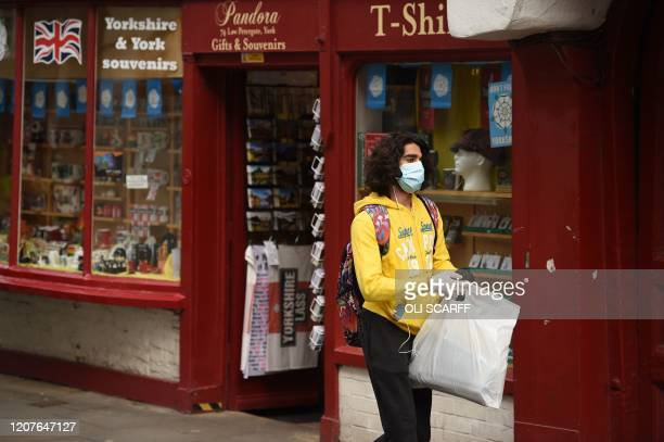 Man wearing a mask and gloves as a precaution against coronavirus is seen coming out of a shop in the centre of York, northern England, on March 19,...