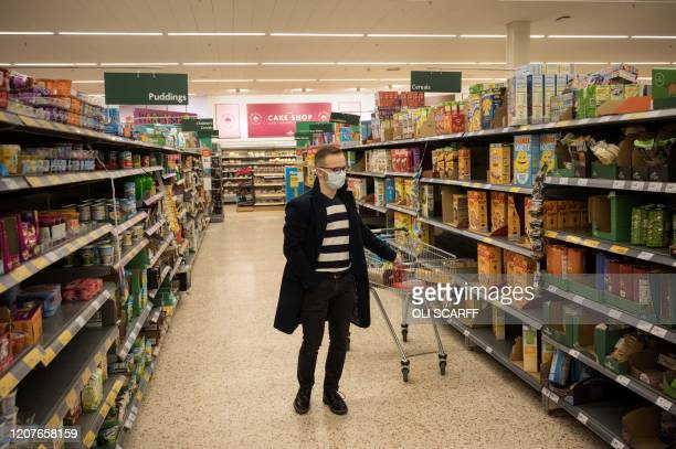 Man wearing a mask as a precaution against covid-19, stands with a shopping trolleys inside a Morrisons supermarket in the centre of York, northern...