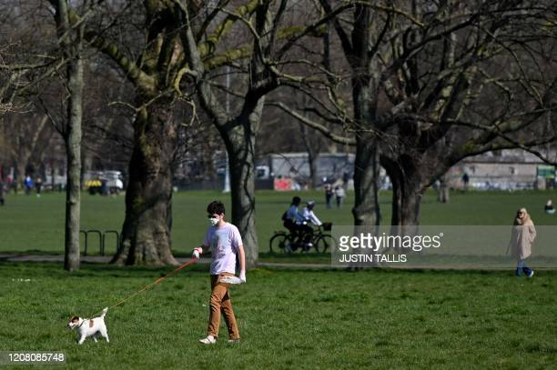 A man wearing a mask as a precautionary measure against covid19 walks a dog on Clapham Common in south London on March 24 2020 after Britain's...