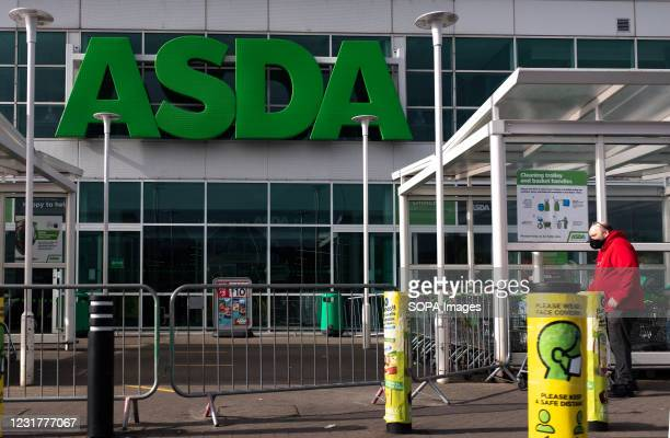 Man wearing a mask as a preventive measure against the spread of covid-19 outside Asda supermarket in Wales, UK. Eight more people have died with...