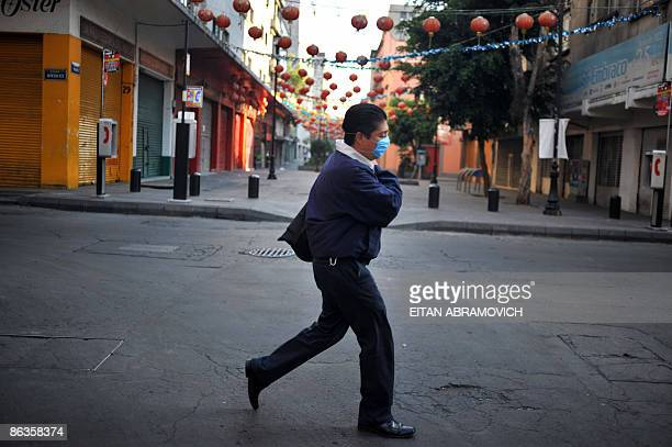 A man wearing a mask crosses an empty street in Mexico City's Chinatown on May 3 2009 The influenza A virus epidemic in Mexico is 'in phase of...