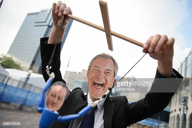 A man wearing a mask depicting leader of the UK Independence Party Nigel Farage dangles puppet representing Conservative Party leader and Prime...
