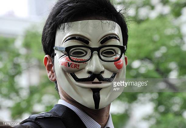 "Man wearing a mask displaying the wording ""Freedom Forever!"" attends a clean up mission organised by hacker collective Anonymous on a street in Tokyo..."