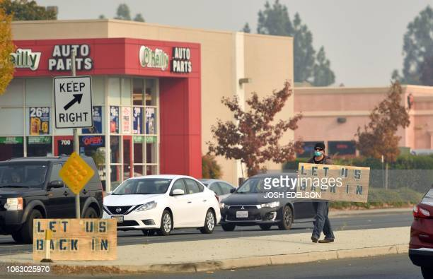 A man wearing a mask due to poor air quality walks on a median holding a sign that requests access to an evacuated area in Chico California on...