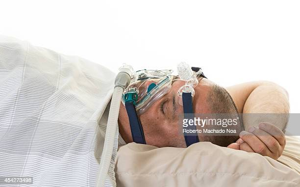 Man wearing a mask for treating sleep apnea Mildly obese man suffering from sleep apnea and having a CPAP treatment