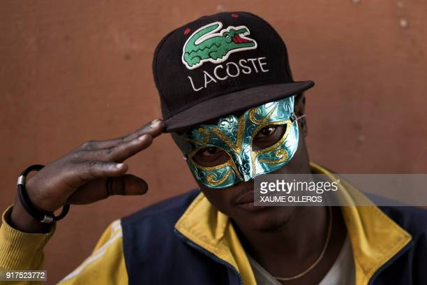 A man wearing a mask gestures ahead of the Bissau Carnival parade on February 12 2018 in Bissau The 2018 edition of the Bissau Carnival celebrating...