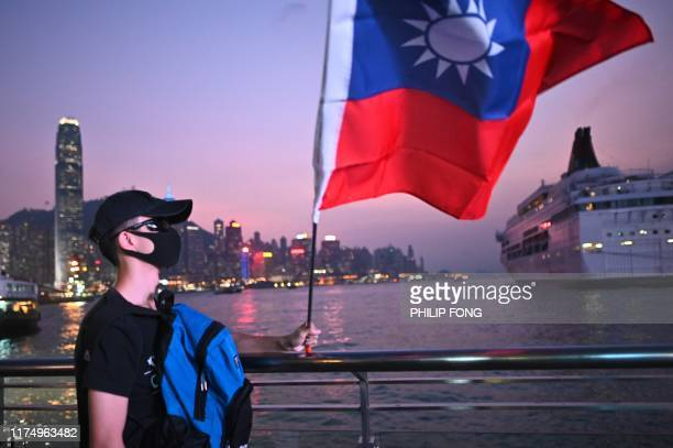 A man wearing a mask holds a Taiwanese flag as he joins others at a rally to mark Taiwan's National Day in the Tsim Sha Tsui district in Hong Kong on...