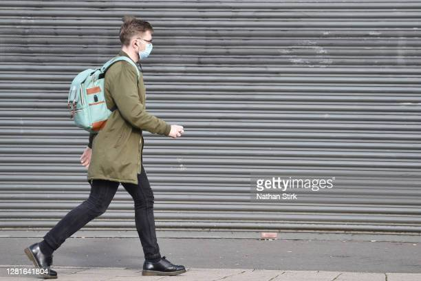 A man wearing a mask is seen walking past a closed shop as StokeonTrent prepares to move up to High Covid Alert Level on October 22 2020 in Hanley...