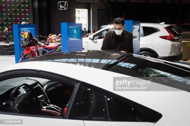 Man wearing a mask looks at a car on February 28, 2020 at the Geneva International Motor Show which has been cancelled due to the Covid-19 epidemic....
