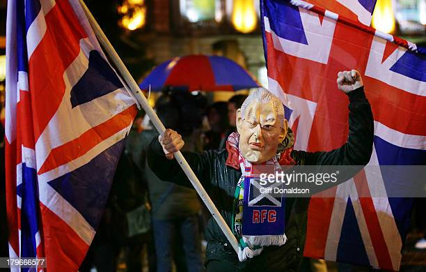 CONTENT] A man wearing a mask of Rev Ian Paisley the former Northern Ireland First Minister takes part in continuing protests outside Belfast city...