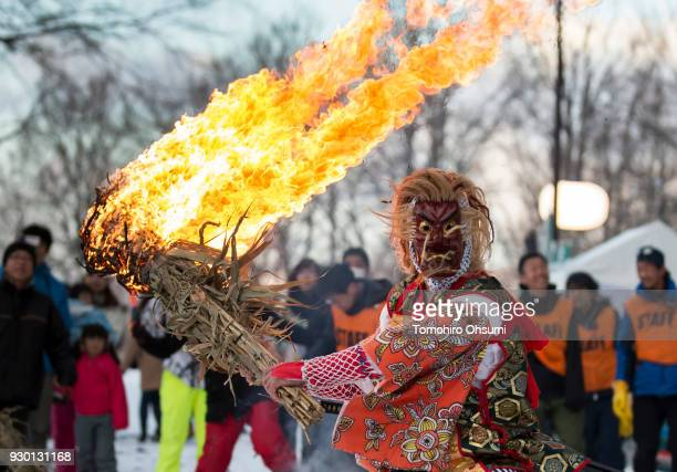 A man wearing a mask of Tengu a legendary creature in Japanese folklore holds a flaming torch during a ceremony held ahead of the Tsunan Sky Lantern...