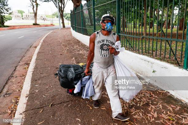 A man wearing a mask outside the gates of Ibirapuera Park walks during a lockdown aimed at stopping the spread of the coronavirus pandemic on March...