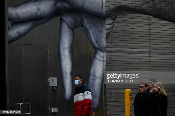 A man wearing a mask passes a mural in Manhattan on March 14 2020 in New York City The World Health Organization said March 13 2020 it was not yet...