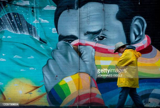 """Man wearing a mask passes a mural on April 13, 2020 in New York City. - New York's governor declared April 13, 2020 that the """"worst is over"""" for its..."""