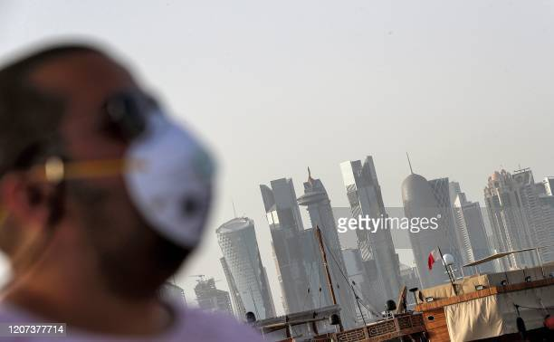 A man wearing a mask precaution against COVID19 coronavirus disease walks along the Doha corniche in the Qatari capital on March 16 2020 The six...