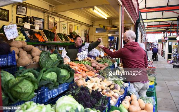 Man wearing a mask purchases fresh fruit and vegetables groceries at Stockport Market on March 12, 2021 in Stockport, England.