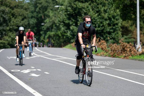 Man wearing a mask rides a bicycle in Prospect Park as the city continues Phase 4 of re-opening following restrictions imposed to slow the spread of...