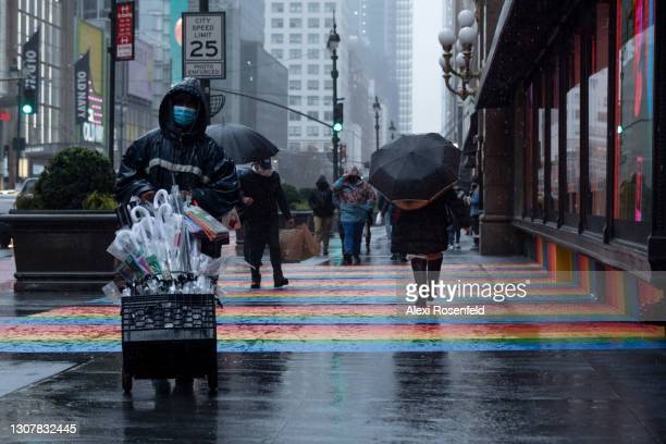 Man wearing a mask sells umbrellas near a rainbow colored sidewalk part of Lacoste's window display at Macy's Herald Square on March 18, 2021 in New...
