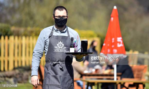 Man wearing a mask serves drinks whilst in a beer garden at Hotel Rudyard on April 12, 2021 in Leek, England. England has taken a significant step in...
