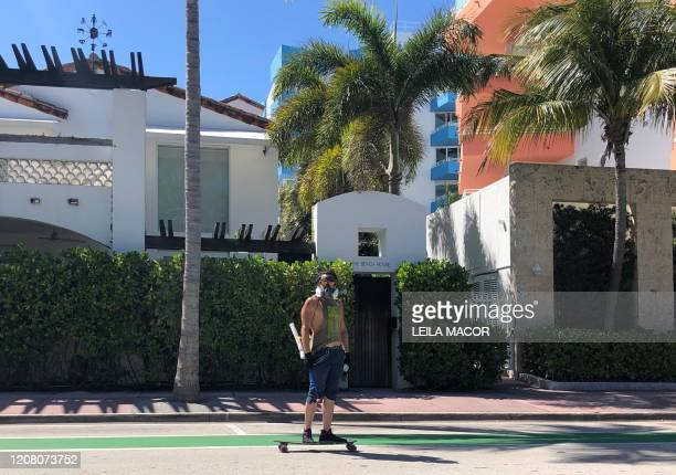A man wearing a mask skateboards in the streets of Miami Florida on March 23 ahead of the stay at home order effective midnight tonight Miami Beach a...