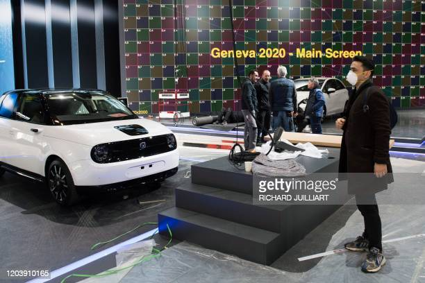 A man wearing a mask stand near a car on February 28 2020 at the Geneva International Motor Show which has been cancelled due to the Covid19 epidemic...