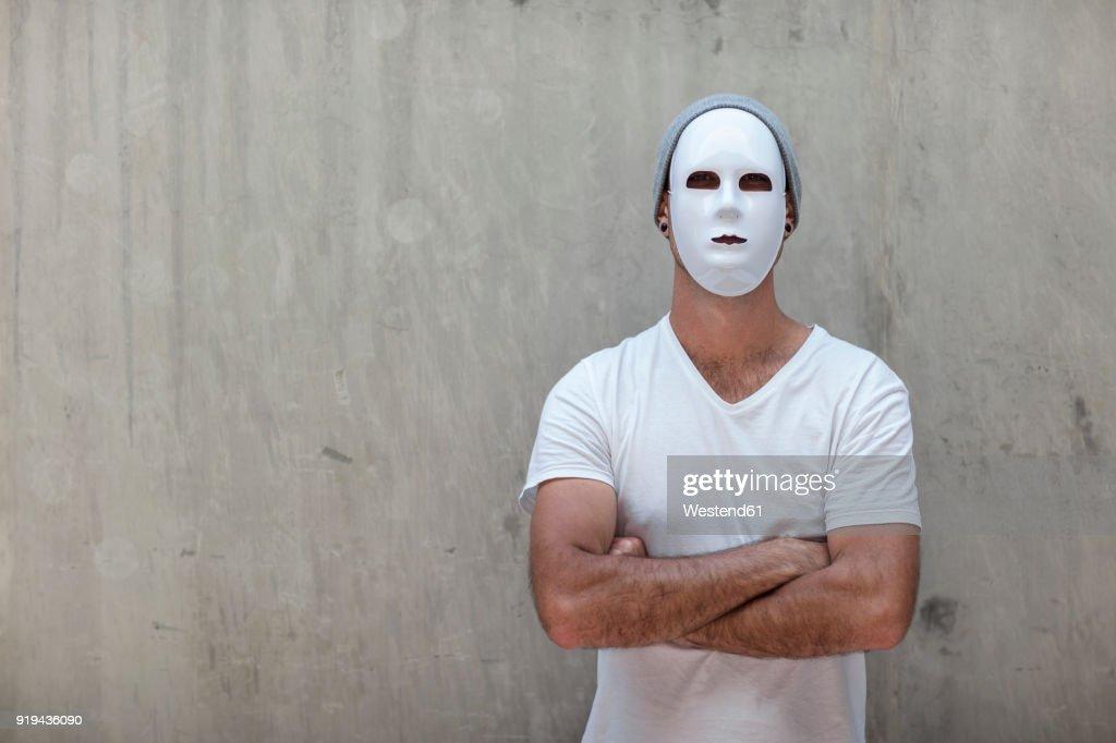 Man wearing a mask standing next to a concrete wall : Foto de stock