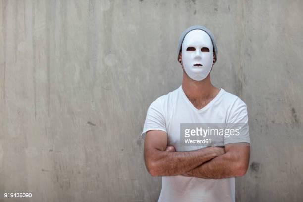 man wearing a mask standing next to a concrete wall - schutzmaske stock-fotos und bilder